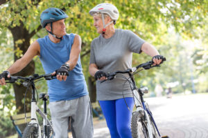 Senior couple walks with bicycles in the park.