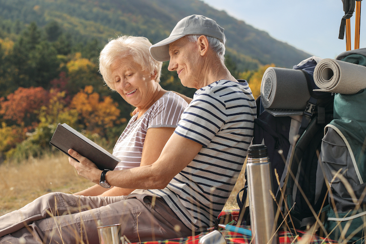 Senior couple reads a book on a mountain.