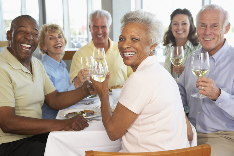 Happy seniors toast with red wine