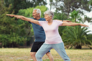 Active senior couple stretching in the park.