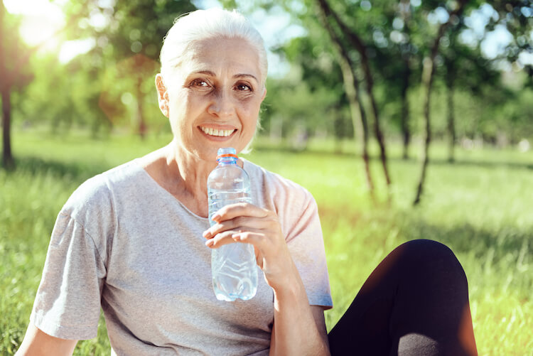 A senior woman enjoys a refreshing glass of water to stay hydrated.