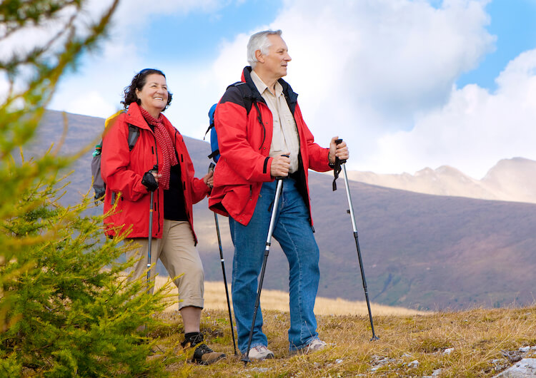 An active senior couple hikes in Glacier National Park.